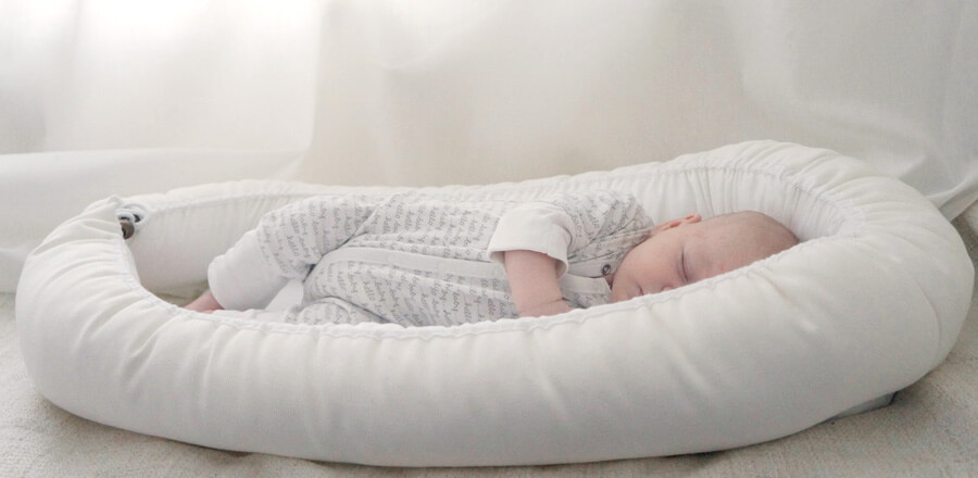 Söpö vauva nukkuu äidin ja isän kanssa sängyssä, Bebiboo unipesässä